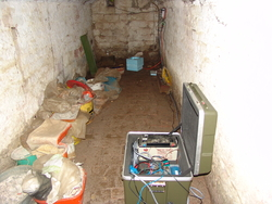 TIMO2 recording station. Typical temporary recording station in the cellar of a building. The seismometer is in the background inside the blue isolation box. The datalogger, battery and other components are inside the green box. At most stations the raw data are stored in a hard disk which is changed every 2-3 months. Author: J. Ritter / W. Scherer